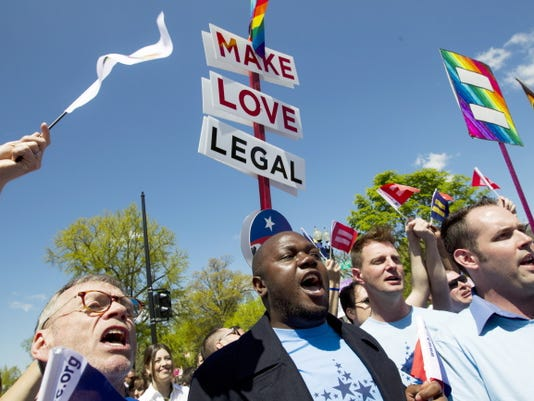 Demonstrators rally in front of the Supreme Court in Washington, Tuesday, April 28, 2015, following historic arguments before the court over the right of gay and lesbian couples to marry.
