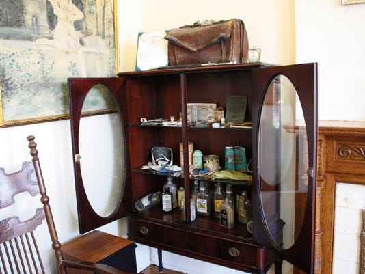 Terry Hammond filled this cabinet with items discovered in the basement while the home was being refurbished. The items include glass bottles and a leather bag.