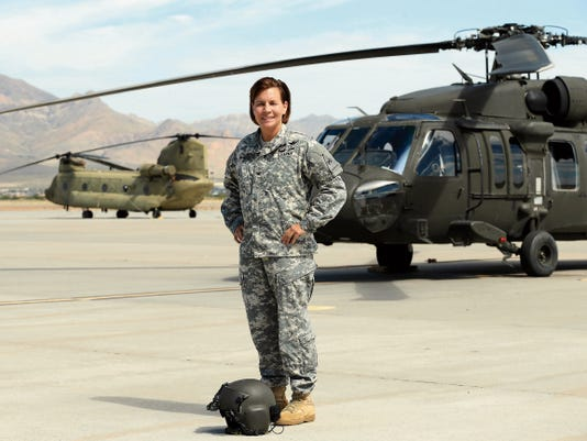 Col. Carey M. Wagen, stands in front of a Black Hawk helicopter which she will fly for the final time on Thursday, July 16th as the Combat Aviation Brigade's commander. She will be given the Aviators' Water Canon Salute for her final flight.