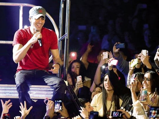 File photo - Enrique Iglesias sits on the edge of stage and performs one of his opening songs while in concert at the Don Haskins Center on Jan. 27, 2015.