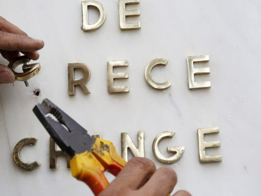 A worker adds a letter on the French logo of National Bank of Greece branch in Athens, Wednesday, July 1, 2015. Greece's government pressed ahead Wednesday with its plan to put austerity measures to voters after European creditors rebuffed its latest proposal for a new aid program.(AP Photo/Petros Karadjias)