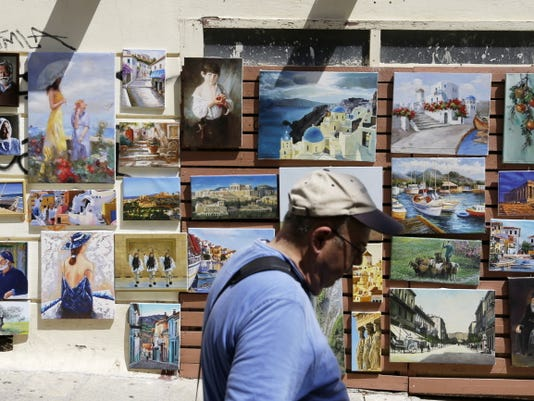A man passes a shops with  paintings of scene of Greece Tuesday in the Plaka tourist district of Athens.