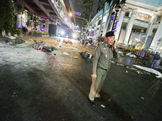 A police officer stands in the middle of Rajprasong Intersection in front of the Erawan Shrine after an explosion in Bangkok, Monday, Aug. 17, 2015. A large explosion rocked a central Bangkok intersection during the evening rush hour, killing a number of people and injuring others, police said.