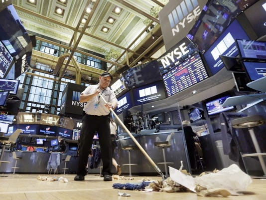 Raul Rodriguez sweeps the floor of the New York Stock Exchange after the close of trading, Friday, Aug. 21, 2015.  The Dow Jones industrial average fell to 16,459.75, and ended down 3.1 percent on Friday. The Standard & Poor's 500 index dropped 64.84 points, or 3.2 percent, to 1,970.89.  (AP Photo/Richard Drew)