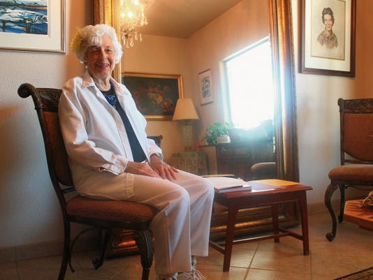 Lyn Brooks sits  in her home, where she hosts a meditation circle every Monday. Brooks says she always wears a flower in her hair when she leads a circle.