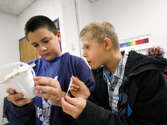Ethan Russell and Wyatt Gleesing, fifth-graders at Heights  Elementary School, collaborate to secure pipe cleaners on their group's prototype.