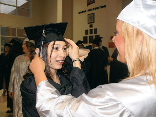 Angelina Garcia gets help straightening her mortarboard from fellow graduate Samantha Nowell. Garcia and Nowell were part of Academy Del Sol's graduating class of 2015 and were celebrated Thursday evening at the Tays Center.