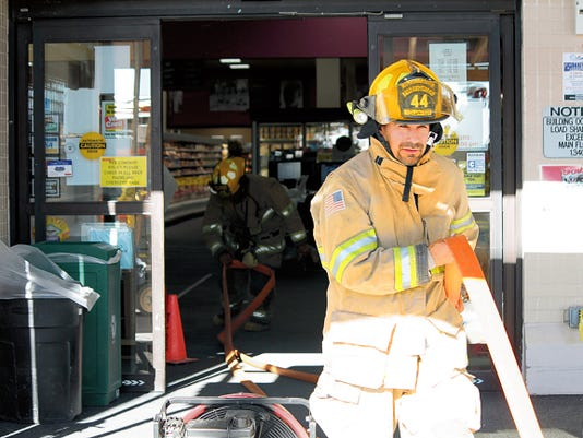 Firefighters with the Alamogordo Fire Department carried a length of house out the front entrance of the Lowes Grocery after extinguishing a fire in the store's tortilla oven. AFD Deputy Chief Jim LeClair said fans stationed at the entrance created positive pressure to push the smoke out the north side of the building.
