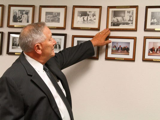 Otero County attorney Daniel A. Bryant looks at pictures of former commissioners that he has worked with over the years. Bryant was appointed by Gov. Susana Martinez to the 12th Judicial District Court judge's seat in Carrizozo Friday.