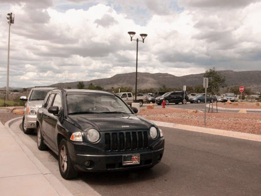 A line of cars pull in to the pickup and drop off loop in front of Desert Star Elementary School on Washington Avenue.