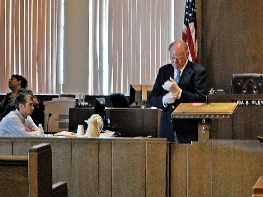JESSICA ONSUREZ CURRENT-ARGUS   Defense attorney Kenneth Wilson, right, prepares to review evidence during the testimony of state's witness Steven Guerra, an expert on firearms and tool marks from the New Mexico Public Safety Department's forensic lab. Dallas Hnulik, left, has been charged with first degree murder in the 2010 death of Brandy Capps.