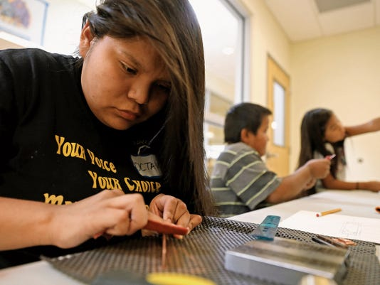"""Octavia Joe, 17, of Farmington, makes a bracelet on Wednesday during the Dahayóígíí youth art event at the Shiprock Youth Complex. """"Dahayóígíí"""" means """"the strong ones"""" in the Navajo language. The three-day event started Wednesday and continues through Friday. It is aimed at introducing traditional forms of Navajo art to the next generation. Workshops on Wednesday focused on jewelry design, sandpainting, basketry, rug weaving, sculpture, beadwork, performing arts and pottery."""