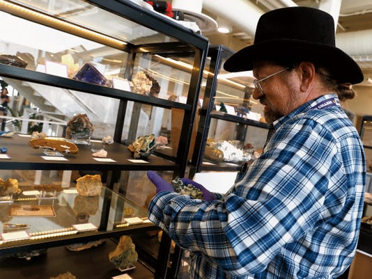 Jeff Self, curator for the San Juan College Sherman Dugan Museum of Geology, prepares a display case on Aug. 31 at the museum, which is located inside the college's School of Energy in Farmington.