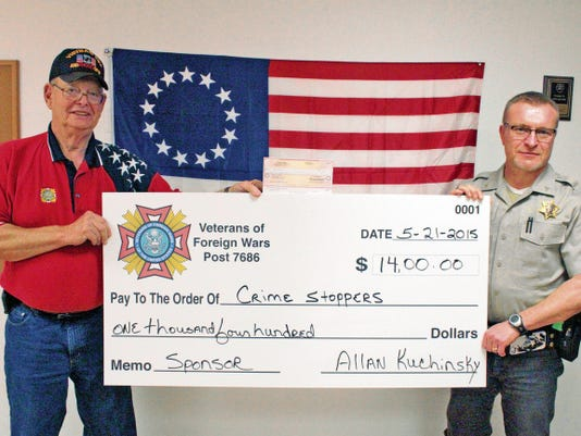 """Quartermaster Allan Kuchinsky presented Otero County Crime Stoppers with a 1,400 check from the Veterans of Foreign Wars Post 7686 Thursday. Crime Stoppers Law Enforcement Director T. O. Livingston accepted the award on behalf of the program at the VFW Office. Livingston said that the VFW has been making donations to Crime Stoppers since at least when he began working with the program in 2000. """"They're one of our strongest supporters of the program,"""" he said. The donation will go towards paying informants who help local law enforcement solve crimes."""
