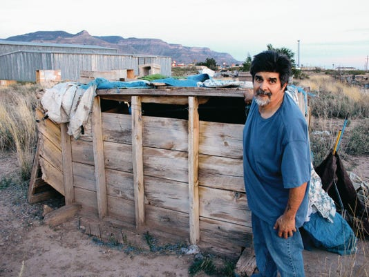 Longtime Alamogordo resident Frank Trevizo, 59, who said he's been homeless since a divorce in the 70s, balanced himself by holding onto the wooden shelter in the desert where he's lived for the last five years. A back injury sustained when a truck hit him causes him to stagger when he walks.
