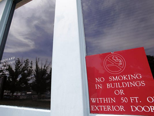 A no-smoking sign is posted Wednesday at the entrance of the School of Trades and Technology building at San Juan College in Farmington.
