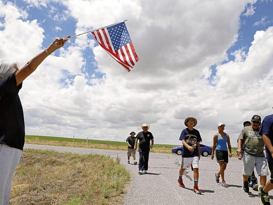 Joan Waters, of Fruitland, holds up an American flag as participants walk down N.M. Highway 371 near Farmington on Friday during the 'Honoring our Women Veterans' walk.