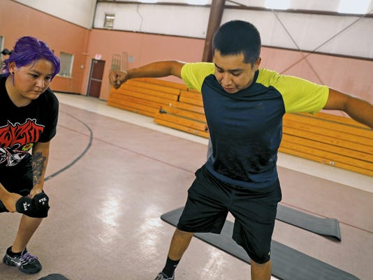 Certified personal trainer Rashaun Nez, 20, of Lower Fruitland, teaches participants how to use weights on Thursday during the free Warrior Fitness Challenge program at the Walter Collins Center in Upper Fruitland.