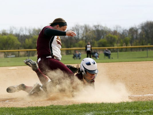 Big Spring's Amily Baker, left, goes to tag a diving Sami Barmont at first base in the Big Spring Tournament final on Saturday. The Bulldogs scored four unanswered runs in the bottom of the seventh inning for a walk-off 8-7 win.