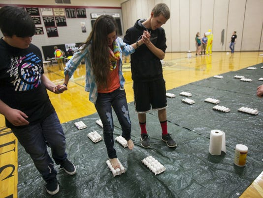 South Western High School freshman Tyler Bateman, left, and Derick Calp, right, help fellow student Myla Arambulo walk on top of cartons of eggs without breaking them during a relay at the Junior Achievement of South Central Pennsylvania's STEM Summit on April 7. The high school hosted the summit for a second year in a row Tuesday to teach students about careers in science, technology, engineering and mathematics.