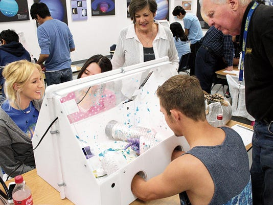 Space Museum Education Director Dave Dooling, at right, looked on while students concluded their dissection of the food-based alien life form in an improvised quarantine facility. The autopsy left blue Jell-O along the interior of the structure, one of the fake body parts which students had to identify at the end of the activity.
