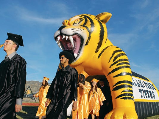 Dillon Dixon and Jacob Eiland walk through the tunnel and onto the field for graduation. Friday's graduation for the class of 2015 was the first in 29 years to be held in the evening for Alamogordo High School.