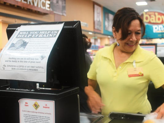 """Lowe's Marketplace cashier Gina Bell checks out a customer Tuesday afternoon. Fliers around the store ask shoppers """"Will you help us help Efrain?"""" Donations are accepted at any First National Bank location in Alamogordo."""