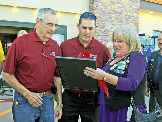 Lowe's Marketplace CEO Roger Lowe, center, is given a welcoming certificate by Alamogordo Chamber of Commerce Board Chair Regina Colbert.