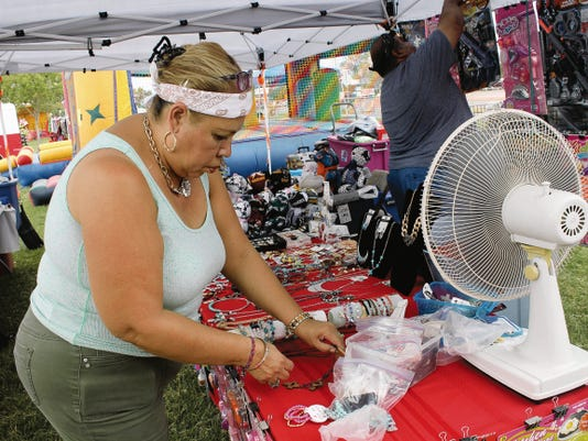 Lety and Juan Fernandez set up the JNL Toys and Novelties booth on Friday afternoon. The Fernandez's are from El Paso. The booth offers toys and other novelty items for every age group at the 25th annual Cottonwood Arts and Crafts Festival.