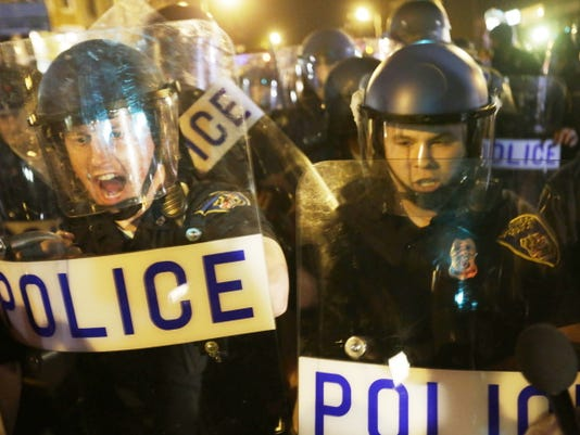 Police in riot gear push back on media and a crowd gathering in the street after a 10 p.m. curfew went into effect Thursday, April 30, 2015, in Baltimore. The curfew was imposed after unrest in the city over the death of Freddie Gray while in police custody.