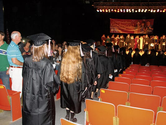 KATIE ENGLAND - CURRENT-ARGUS   Students at NMSU Carlsbad filed past family members and friends during the commencement ceremony on Friday.