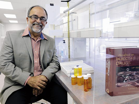 José O. Rivera, the founding dean of the UTEP School of Pharmacy, sits at a desk in one of the school's labs. Rivera is the director of the UTEP-UT Austin Cooperative Pharmacy Program.