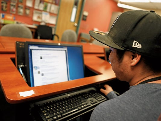 EDGE student Tyler Bellison looks over the New Mexico Institute of Mining and Technology website on Monday in the EDGE program office at San Juan College in Farmington.