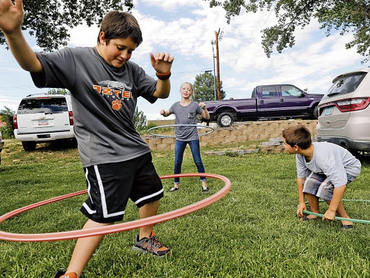 From left, Nicholas Martinez, Hannah Deenihan and Kaiden Mills play with hula-hoops on Tuesday at the Girl Scouts of New Mexico Trail's booth during Aztec's annual National Night Out event at Minium Park in Aztec. The Aztec Police Department organizes the annual community outreach event.