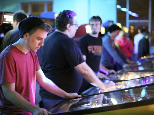 Drew Johnson, 18, of Hanover, plays pinball along with a crowd of about 50 at Timeline Arcade's re-opening near Center Square in 2013.