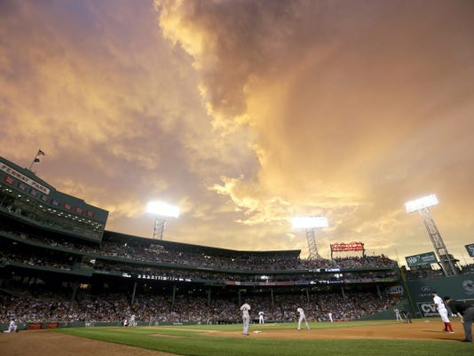 The Baltimore Orioles play the Boston Red Sox in the fourth inning of a baseball game under a dramatic sky at Fenway Park, Tuesday in Boston. Severe thunderstorm warnings were issued at mid-evening Tuesday for a new line of storms moving across western and north central Massachusetts and northern Connecticut.