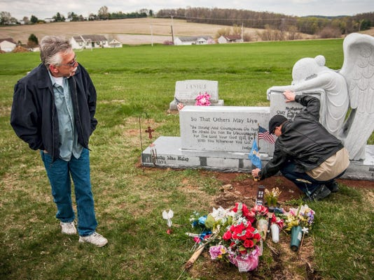 "Earl Haley, left, father of late firefighter Cory Dane Haley, looks over a newly-installed headstone near the North Hopewell-Winterstown Volunteer Fire Company Station 45 as Todd Armold, a second cousin to Cory, arranges a flag by the grave on Thursday. Haley remembered his son, who died Dec. 24, 2013, as the bravest man he ever knew. ""He loved firefighting and he loved Jesus,"" Earl Haley said."