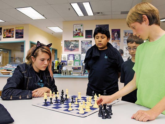 Katerina Williams and Caleb Martin play for the Middle School District Chess Championship, while Kai Ulukita and Steven Broaddus watch.