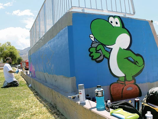 Billy Copeland takes a break from painting Yoshi on the side of the ramp and works on joining his and Montoya's Pac-Man pieces together to make one mural. Copeland was one of the many community members participating in Alamogordo CLub for Teens' Art in the Park event Saturday.