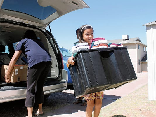 Jasmine Sisson carries donations into Love Inc. made by Girl Scouts of the Southwest Council on Thursday morning. The Girl Scout troop gave 200 in donated goods including kitchen towels, dish cloths, wash cloths, toothbrushes, combs, pillows, peanut butter, syrup and spoons.