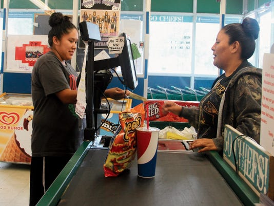 A woman buys hot Cheetos and a large soft drink at the Tribal Store in Mescalero.