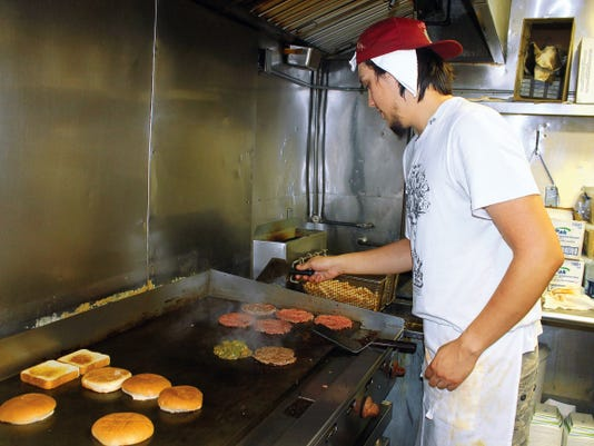 Hi-D-Ho Drive-In Cook, Eli Martinez, flips burgers and prepares green chile to top them off. The establishment at 414 S. White Sands Blvd. was named a top spot for tourists to visit to have New Mexico's classic dish.