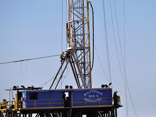 JESSICA ONSUREZ - CURRENT-ARGUS.   Two workers climb up a derrick on a rig in Loving in August 2014.