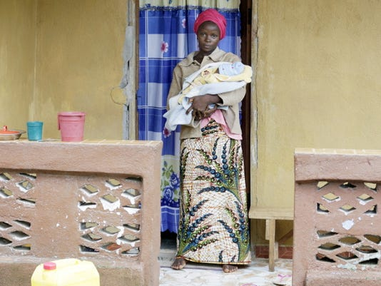 Ebola survivor Victoria Yillia stands with her newborn son Barnabas outsider her home Aug. 16 in Kenema, on the outskirts of Freetown, Sierra Leone.