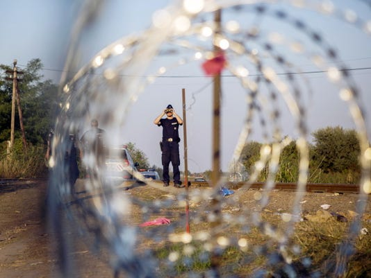 In this Tuesday, Sept. 1, 2015 file photo, a Hungarian police officer looks through binoculars as he checks the border for refugees entering the country illegally next to the town of Roszke, Hungary. In the 28-nation EU, some countries have sought to block the unprecedented flow of migrants fleeing war or poverty in the Middle East and Africa.