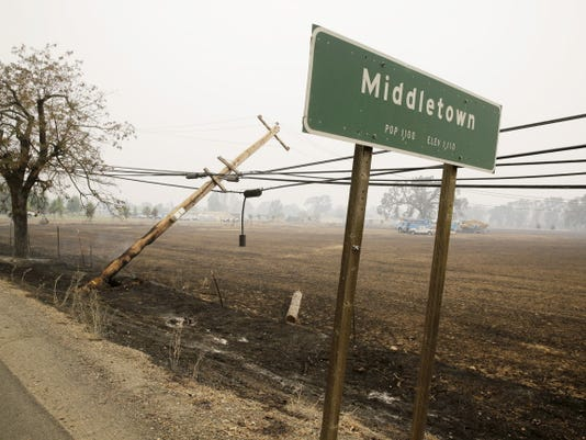 A downed power pole continues to burn along Highway 29 Sunday, Sept. 13, 2015, in Middletown, Calif. Two of Californiaís fastest-burning wildfires in decades overtook at several Northern California towns, destroying over a hundred homes and sending residents fleeing Sunday.