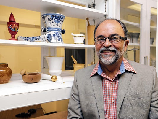 José O. Rivera, the founding dean of the UTEP School of Pharmacy, sits by some of the artifacts donated to the schools program from retired pharmacists. Rivera is currently the director of the UTEP-UT Austin Cooperative Pharmacy Program, where students spend half their time at UTEP and the other at the UT campus.