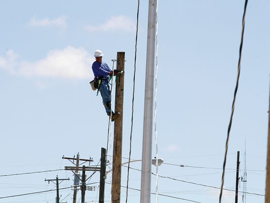 A worker with the Farmington Electric Utility System works on installing new power lines on June 12 near Boyd Park in Farmington.