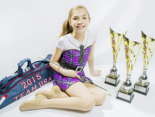 Alaina Rongione, 10, of Littlestown, poses with her trophies and equipment April 12. Alaina won gold in the juvenile division for solo, freestyle and duet performances at the World Federation of National Baton Twirling Associations championship in Lignano Sabbiadoro, Italy, in the first week of April.
