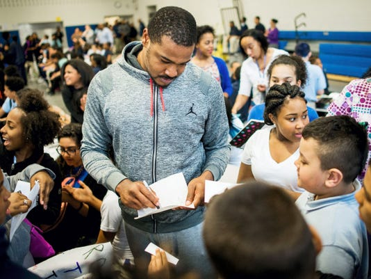 """NFL free agent D.J. Bryant signs autographs on notebook paper for a crowd of students gathered around him during a PSSA """"Rock the Test"""" pep rally at Helen Thackston Charter School on Wednesday. Bryant and Danny Lansanah of the Tampa Bay Buccaneers encouraged the kids to keep good company, work hard at something they love and never give up on their dreams."""